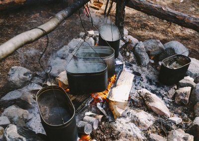 Dinner cooking on a campfire at the base camp. White Irkut River. The Republic of Buryatia. Russia